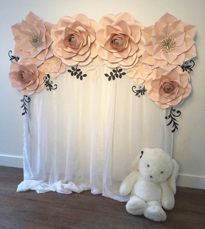 large blush flowers hanging on the wall, on top of white tulle, paper flower wall decor, hanging on white wall, plush bunny on the floor