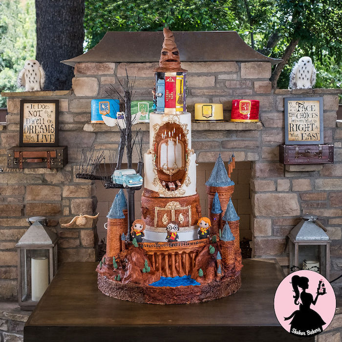 large cake made with different layers, hogwarts books and sorting hat layers, the great hall layer, harrys birthday cake