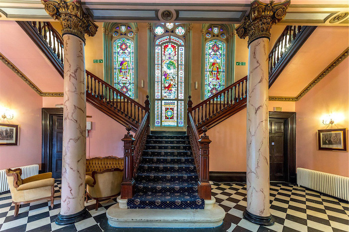 large gothic style staircase, black and white tiled floor, marble staircase with blue carpet, large windows, stained glass window hangings