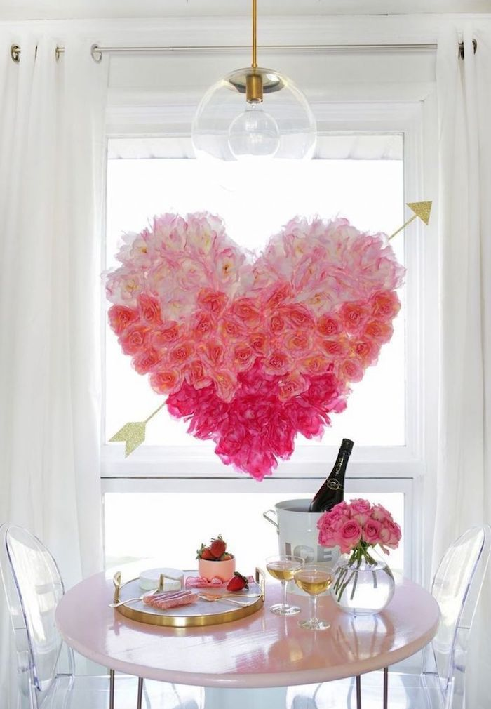 large heart made of pink flowers, hanging over table, set for two with champagne and strawberries, diy valentine decorations