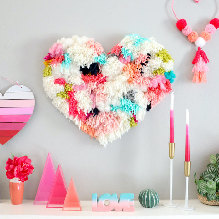 large heart made of pom poms, diy valentine decorations, pink wooden heart, hanging on grey wall, decorations on white surface