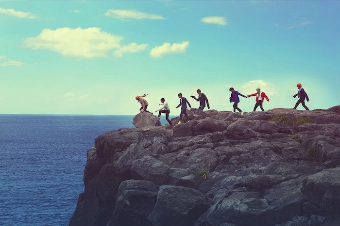 aesthetic phone wallpapers, a group of friends, standing on top of a large rock, next to the ocean, blue sky with white clouds