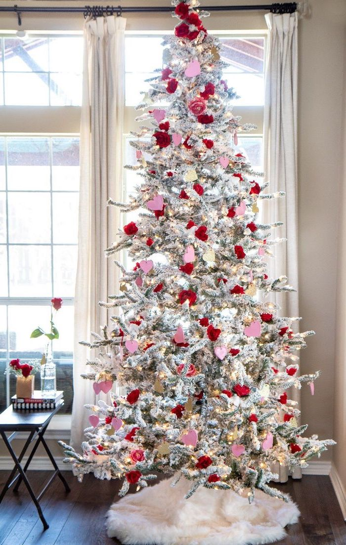 tree with faux snow, decorated with red and pink hearts, outdoor valentine decorations, placed on wooden floor