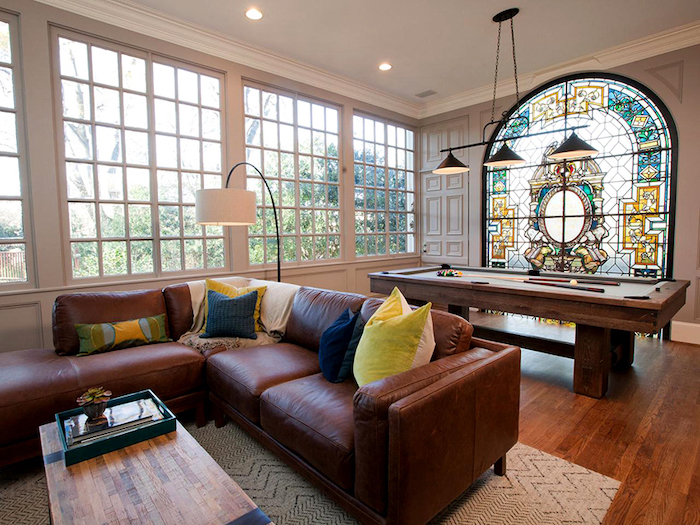 brown leather corner sofa, living room with large windows, leaded glass, pool table, wooden floor and coffee table