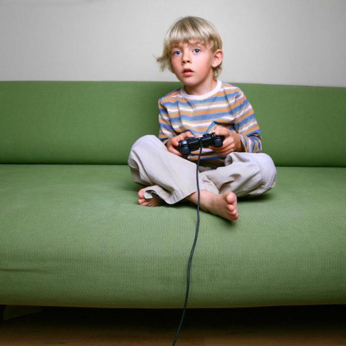 little boy with blonde hair, sitting on green sofa, children's games, playing video games