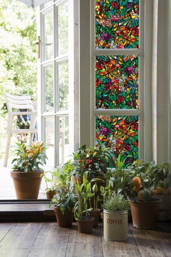 lots of potted plants in different pots, arranged on wooden floor, stained glass window hangings, placed in front of a door