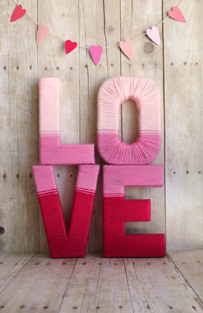 outdoor valentine decorations, hearts garland, hanging on wooden wall, love sign wrapped with pink yarn, placed on wooden surface