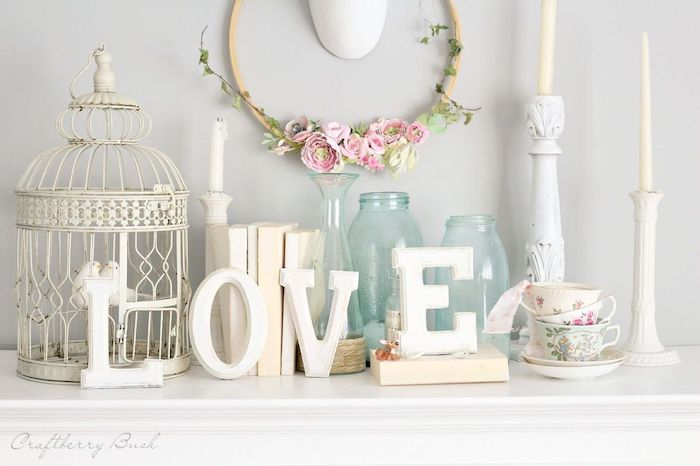 love wooden sign, wreath made with pink flowers, vintage candlesticks and vases, outdoor valentine decorations, arranged on mantel