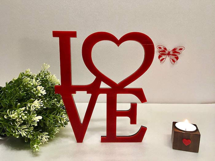 red wooden love sign, valentine lights, small candle and green bouquet next to it, placed on white surface