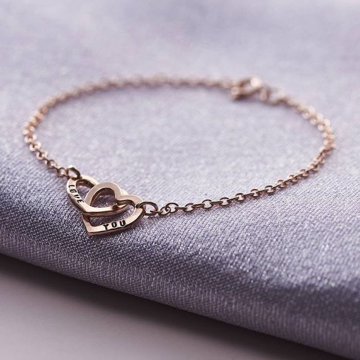 cute valentines day gifts for her, love you personalised bracelet, two connected hearts, placed on grey surface
