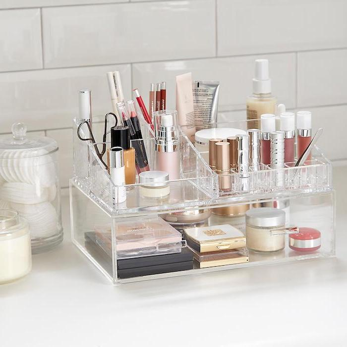 acrylic makeup organiser, cute valentines day gifts for her, lots of different bottles arranged on it, placed on white surface
