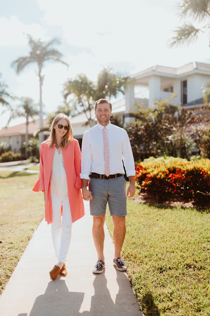 man and woman walking on sidewalk, valentine's day clothes, woman wearing white shirt and pants, long pink coat
