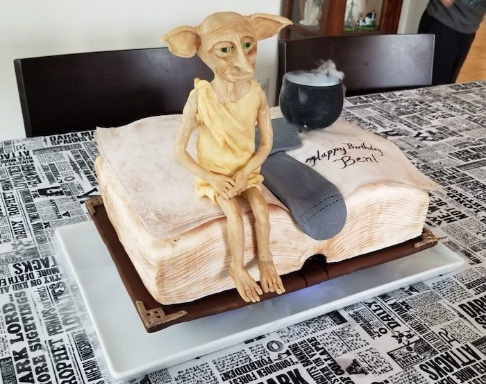 hogwarts cake, cake in the shape of open book, grey sock and dobby made of fondant, placed on top