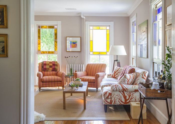 orange armchairs and white sofa in living room, large windows and wooden floors, stained glass window hangings, wooden coffee table