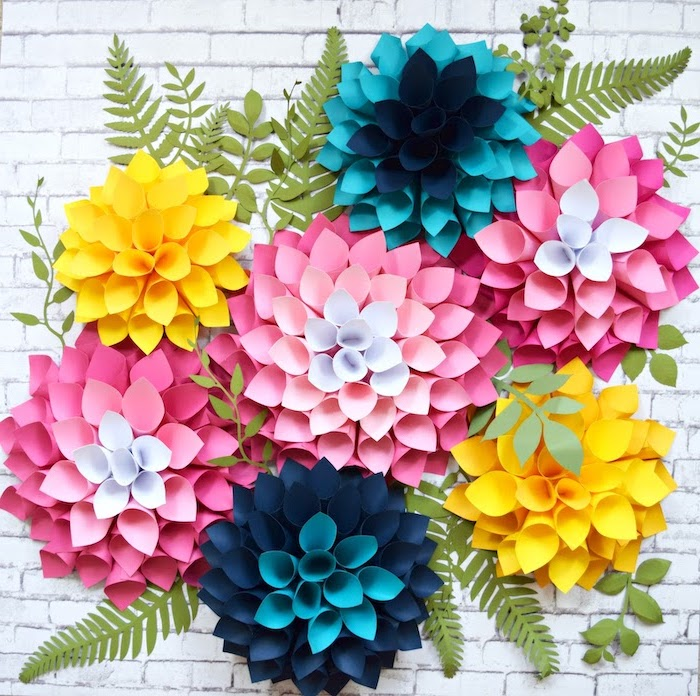 paper flowers in different colors, arranged together on white brick wall, how to make flowers out of tissue paper