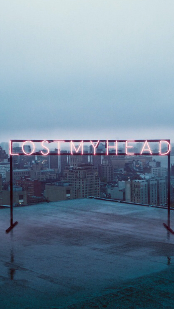 lost my head neon sign, placed on top of a building, dark aesthetic wallpaper, city skyline in the background