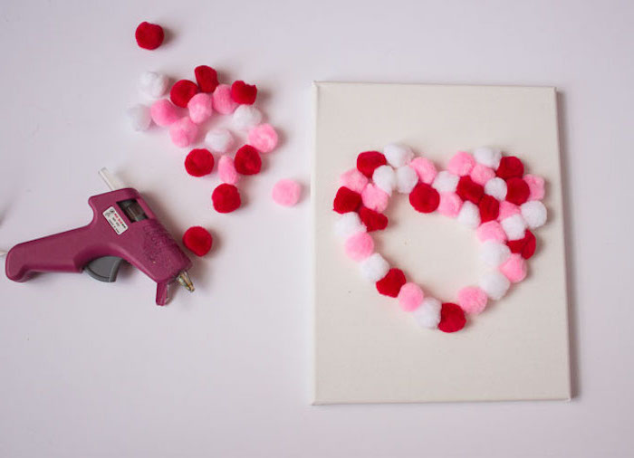 valentine decorations ideas, pink red and white pom poms, glued to a white canvas in the shape of a heart, step by step diy tutorial