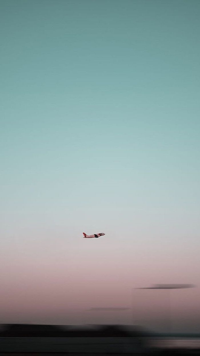 plane flying in the sky, pink aesthetic background, blue and pink sky
