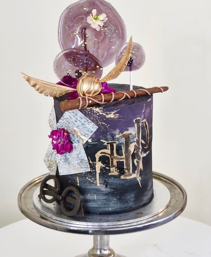 one tier cake, covered with black and purple fondant, hogwarts cake, golden snitch and wand on top