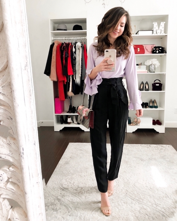 woman taking a selfie in the mirror, wearing black pants, purple blouse, valentine's day clothes, nude sandals