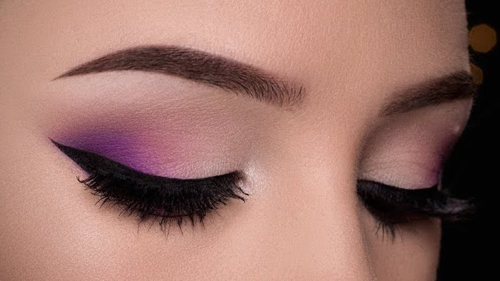 nude and dark pink eyeshadow colors, black cat eyeliner, makeup for beginners, woman with dark eyebrows
