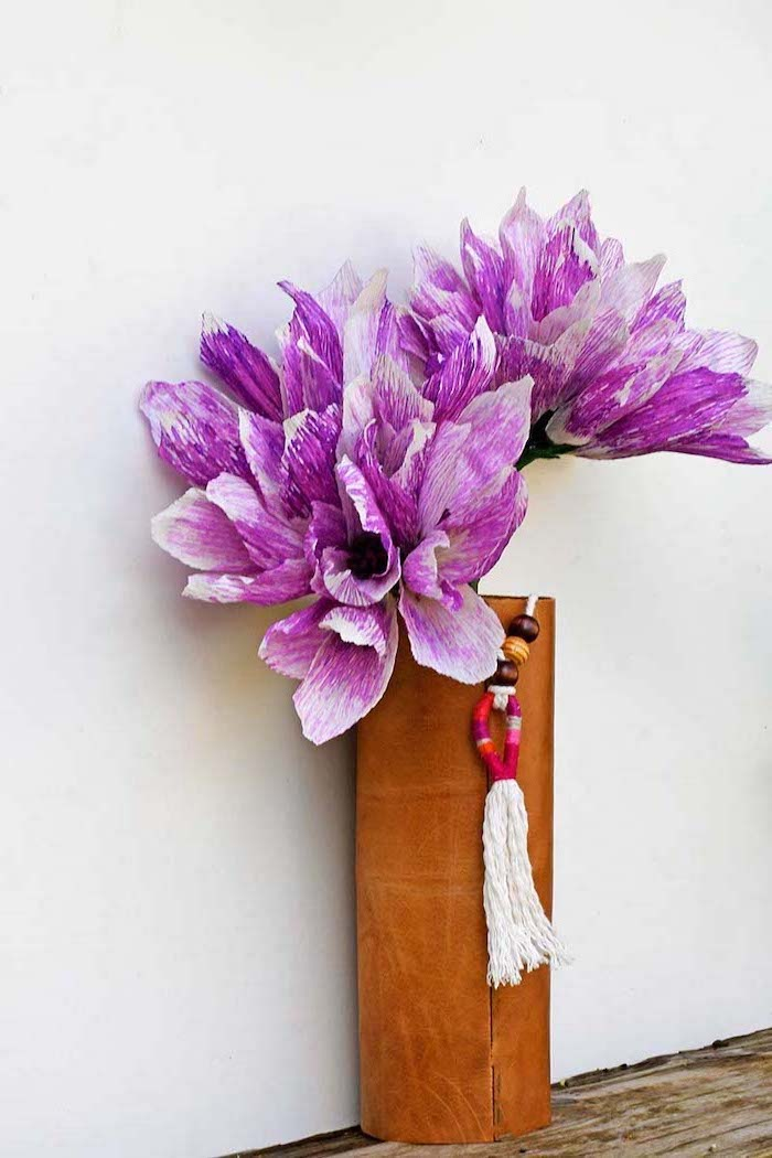 purple and white flowers, made of crepe paper, placed in a leather boho vase, diy paper flowers