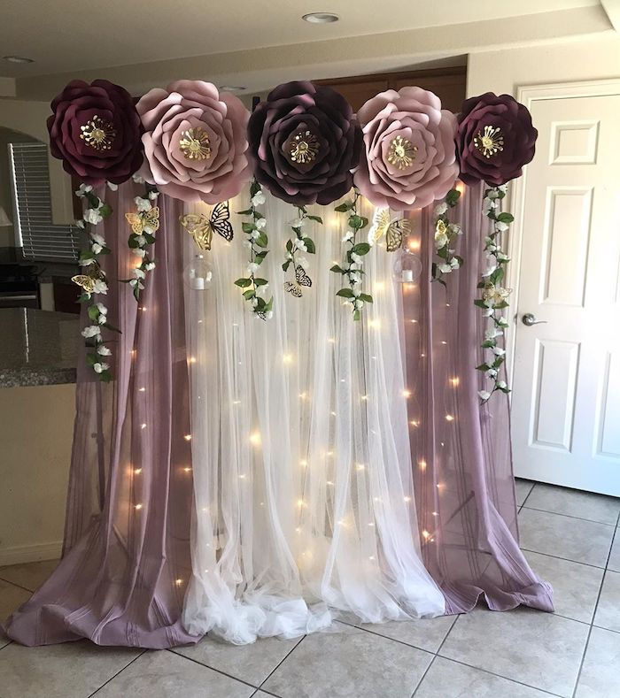 white and purple tulle with fairy lights, giant purple and pink paper flowers on top, diy tissue paper flowers
