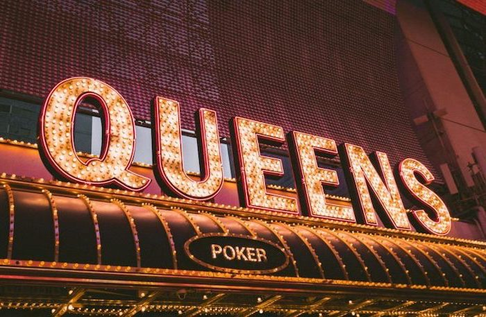queens and poker signs with led lights, aesthetic backgrounds, placed over the entrance of a casino