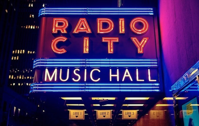 aesthetic phone backgrounds, radio city music hall neon sign, on the side of the entrance, photographed at night