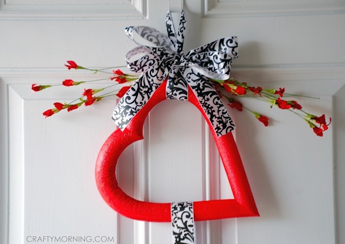 red foam heart tied with black and white satin ribbon, heart decorations, faux red flowers on top, hanging on white door