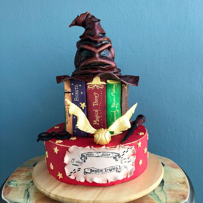 two tier cake made with fondant, sorting hat on top, hogwarts cake, placed on wooden tray, blue background
