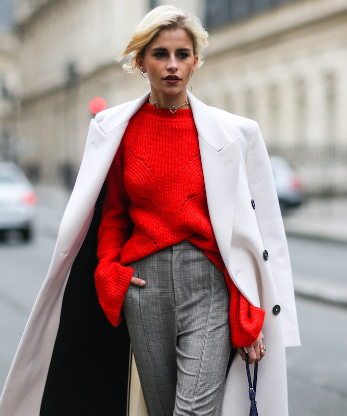 blonde woman wearing red sweater, grey pants and long white coat, valentine's day clothes, walking on the street