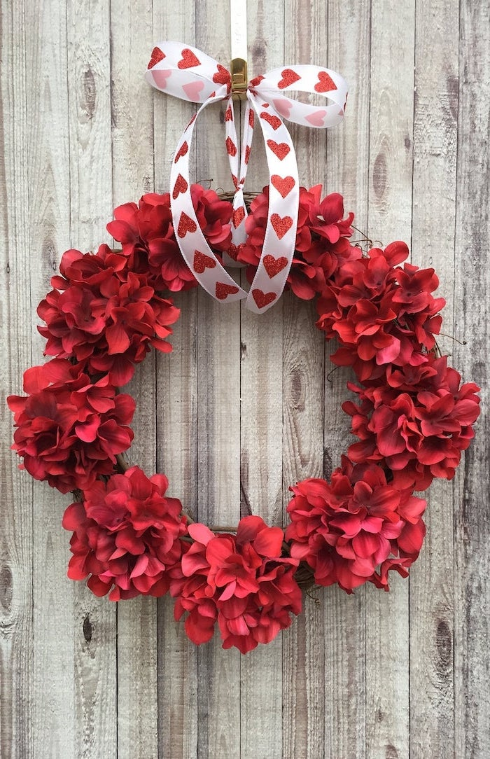 wreath made with red flowers, hanging with white satin ribbon with red glitter hearts, valentine's day home decor