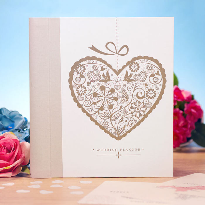 wedding planner with beautiful front cover, valentine day gifts for girlfriend, placed on a wooden surface, flowers around it