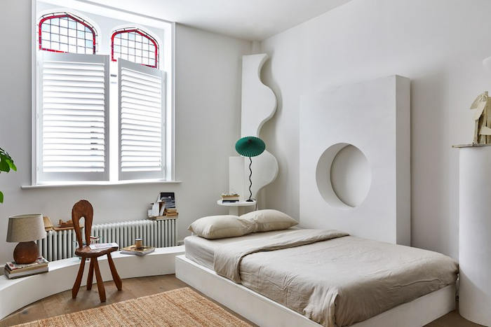 bedroom with single bed, antique stained glass windows, wooden floors and white walls, small wooden chair