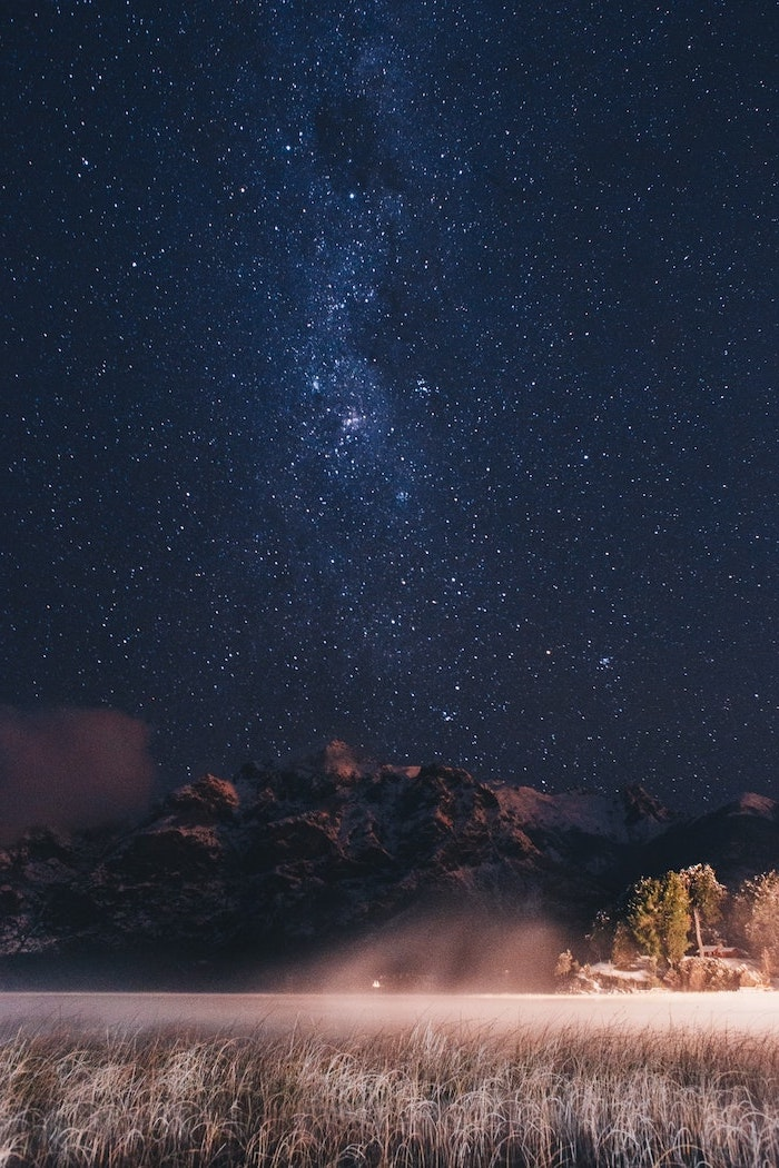 aesthetic lockscreen, dark sky covered with stars, over a snowy mountain landscape