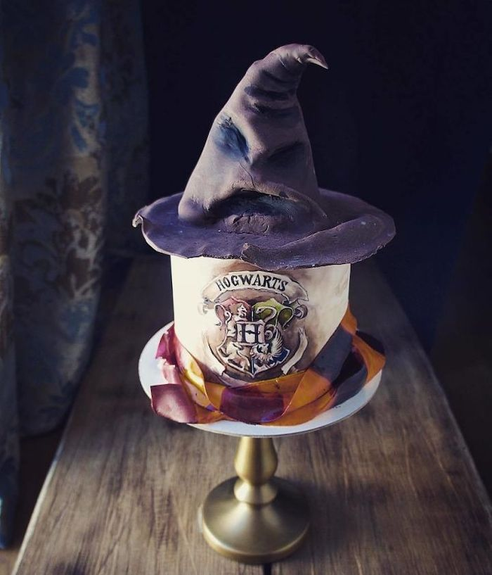 hogwarts cake made with fondant, easy harry potter cake, gryffindor scarf around it, sorting hat on top