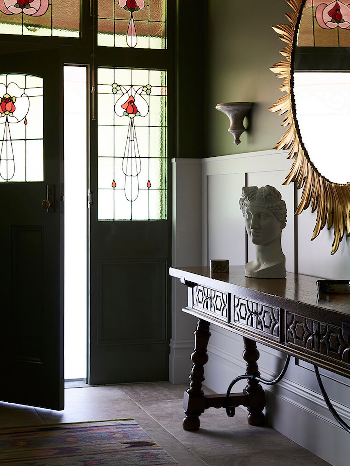 stained glass front door, hallway with wooden table, bust sculpture on it, dark tiled floor with carpet