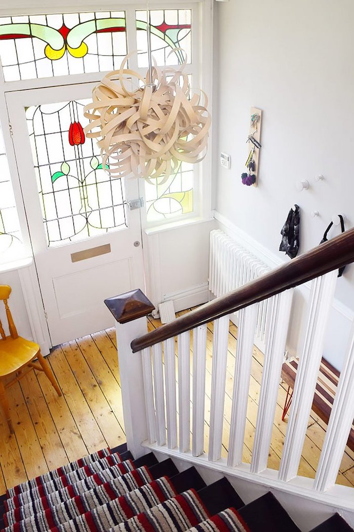hallway and staircase with wooden floor, stained glass front door, dark carpet on the stairs, white walls and lamp shade