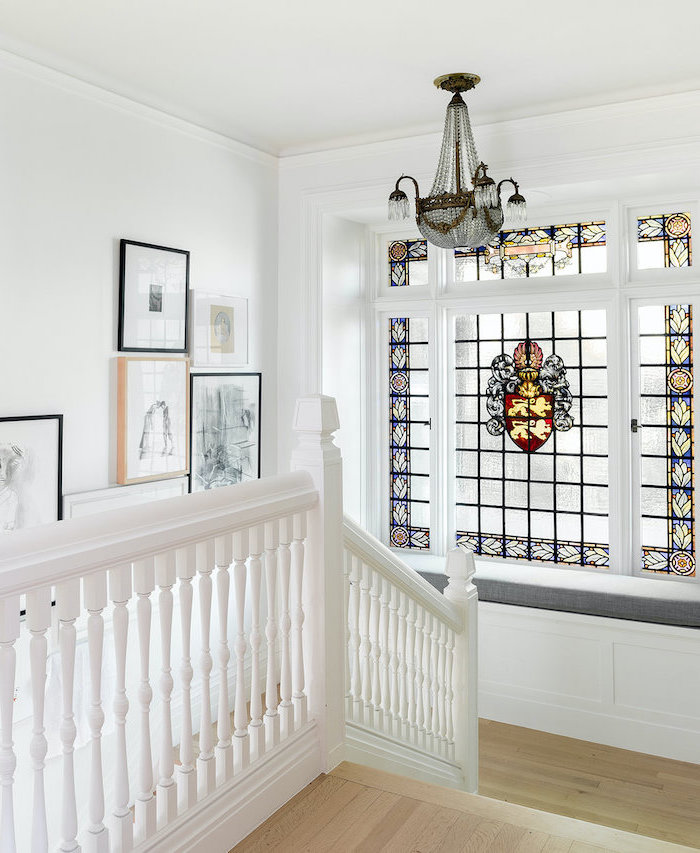 staircase with large window, wooden floors and white railing, stained glass front door, framed art on the wall, vintage chandelier
