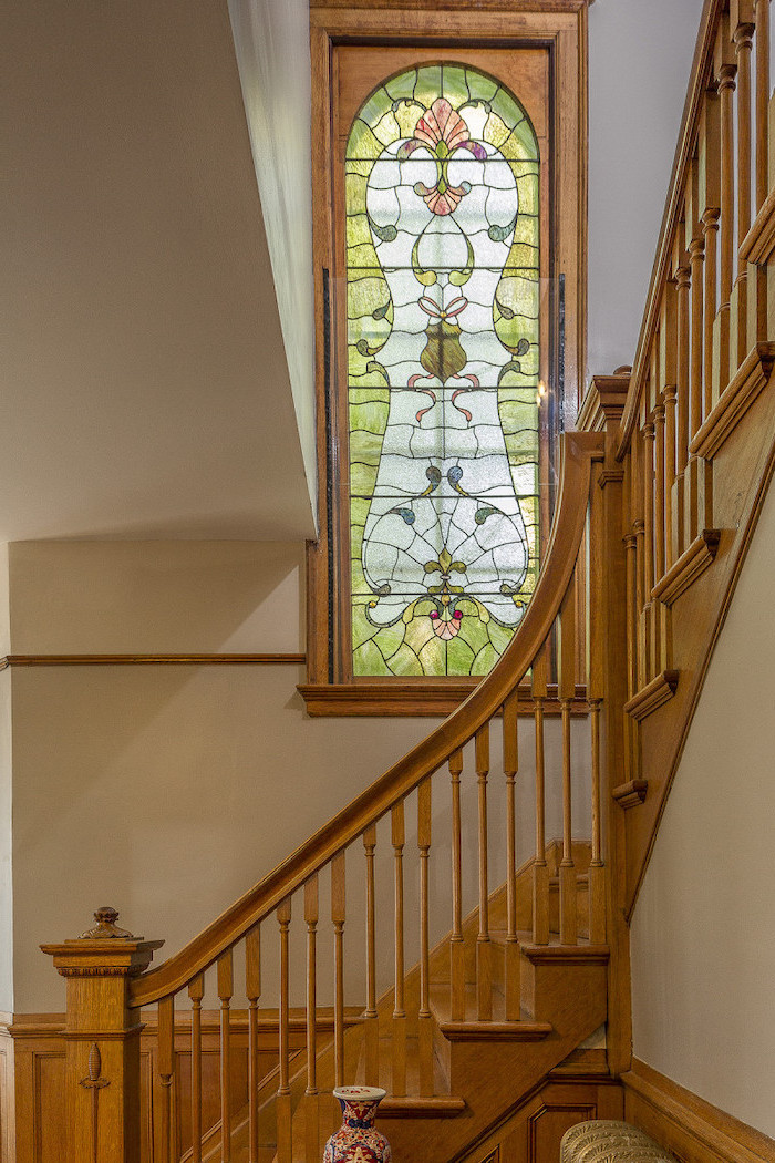 wooden staircase and white walls, stained glass window panels, window between the floor decorated with colored glass