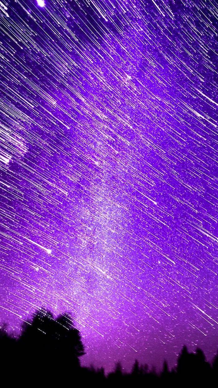 blue aesthetic background, dark purple pink sky, shooting stars across it, dark forest wit tall trees underneath