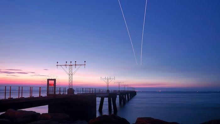 aesthetic computer wallpaper, sunset over a pier, two lines in the sky, airplanes flying above the ocean