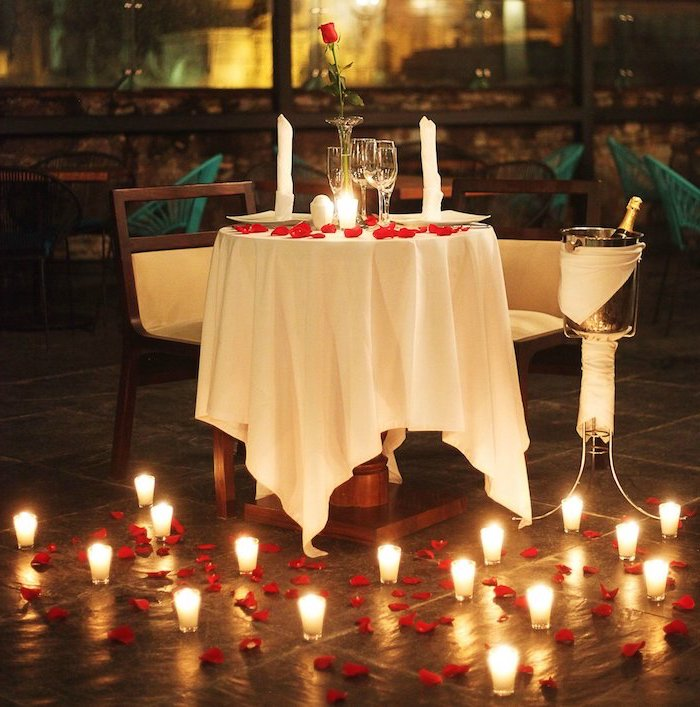 valentine table decorations, dinner table set for two, candles and rose petals scattered on the floor, single rose on the table