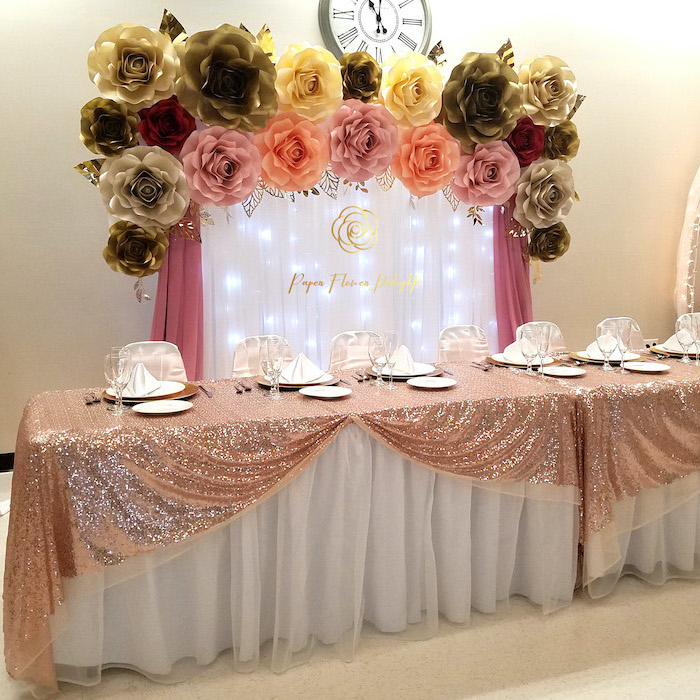 large table covered with rose gold sequinned cloth, diy tissue paper flowers, white tulle with fairy lights, large paper flowers on top