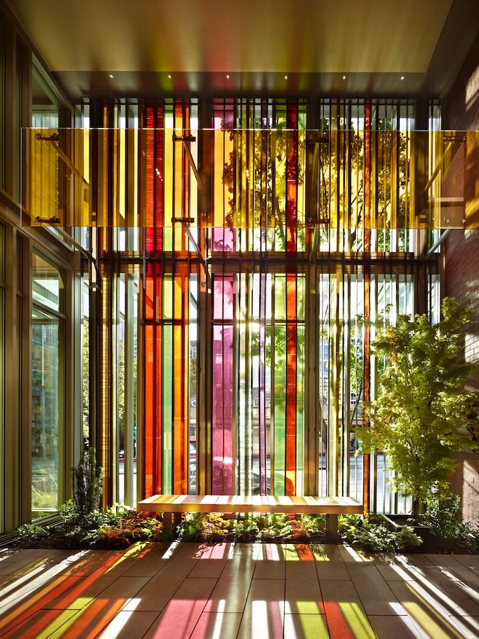 tall windows decorated with different colors, garden with green plants, wooden bench next to it, stained glass window panels