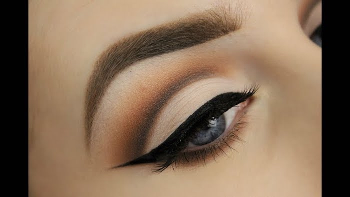 woman with blue eyes, thick light brown eyebrows, nude eyeshadow look, black cat eyeliner