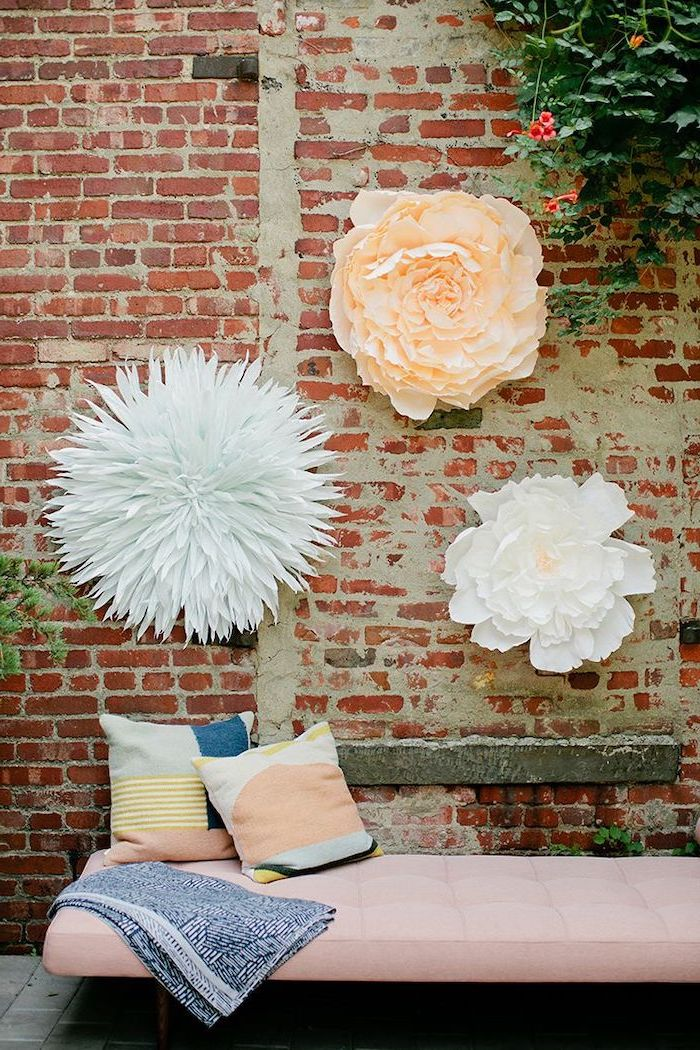 three large paper flowers, hanging on a brick wall, over a pink sofa with throw pillows, how to make paper flowers