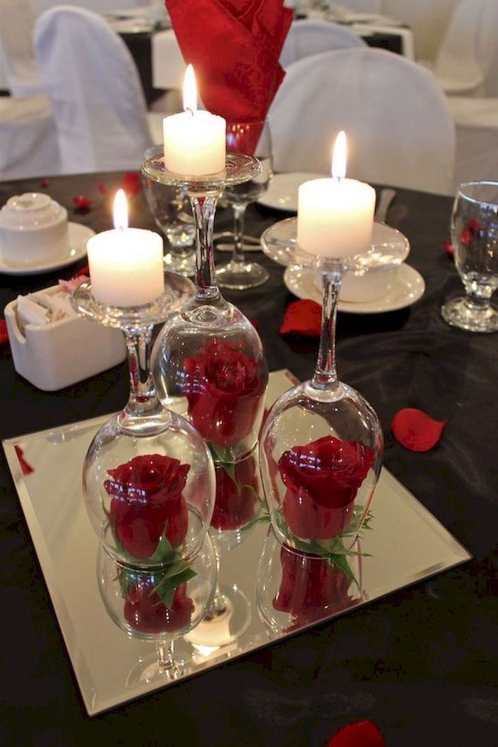 roses covered with wine glasses, candles on top on mirror tray, valentine table decorations, dinner table set for two