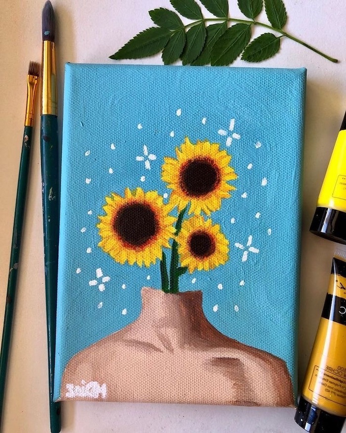 three sunflowers coming out of a mannequin, acrylic painting ideas for beginners on canvas, blue background, brushes around it